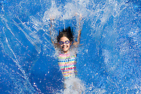 Child splashing in a swimming pool, New Jersey