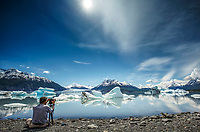 Photographer man takes photo from tripod and shore of ice bergs and Colony Glacier at Inner Lake George. Summer. Southcentral, Alaska.   People/person<br /> <br /> (C) Jeff Schultz/SchultzPhoto.com