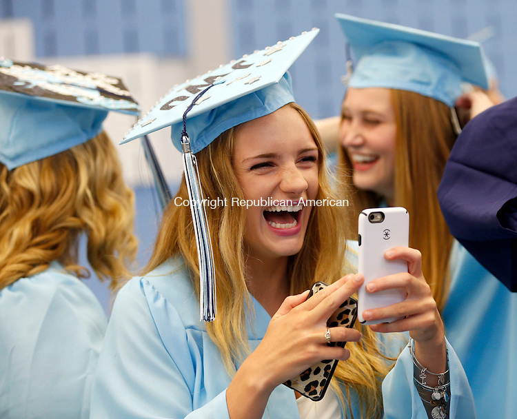 Oxford, CT- 15 June 2015-061515CM13-  Oxford High School graduates Casey Fitzgerald, center, has a laugh with fellow graduates, including Sam Cone, left, and Mackenzie Folsom enjoy a laugh while looking at a cell phone before the start commencement exercises in Oxford on Monday.   Christopher Massa Republican-American