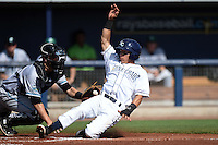 Charlotte Stone Crabs shortstop Andrew Velazquez (1) slides home safely past catcher Joe Hudson (8) during a game against the Daytona Tortugas on April 14, 2015 at Charlotte Sports Park in Port Charlotte, Florida.  Charlotte defeated Daytona 2-0.  (Mike Janes/Four Seam Images)