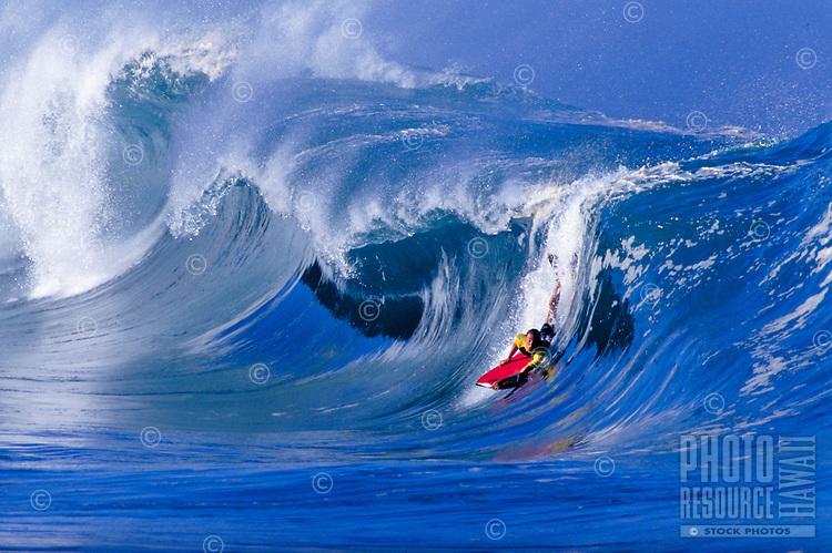 Bodyboarding on the big waves at beautiful Waimea Bay, on the north shore of Oahu.