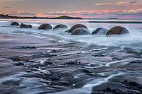 Sunset on beach with Moeraki Boulders, Coastal Otago, East Coast, New Zealand