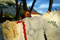 Woman inspecting lace hanging on outside display, in late afternoon light. Makarska, Croatia