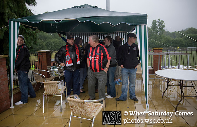 The New Saints 4 Bohemians 0, 20/07/2010. Park Hall Stadium, Champions League 2nd qualifying round 2nd leg. Supporters of Irish club Bohemians taking shelter from the rain under a gazebo outside Park Hall Stadium, Oswestry before their team's Champions League 2nd qualifying round 2nd leg game away to The New Saints. Despite leading 1-0 from the first leg, the Dublin club went out following their 4-0 defeat by the Welsh champions. The match was the first-ever Champions League match in the UK played on an artificial pitch and was staged at the Welsh Premier League's ground which was located over the border in England. Photo by Colin McPherson.