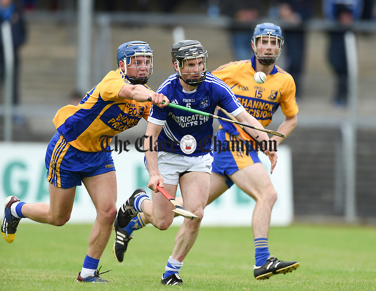 Sean Chaplin of Cratloe in action against Brian Corry and Alex Morey of Sixmilebridge during their game in Cusack Park. Photograph by John Kelly.