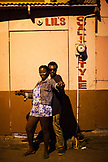 JAMAICA, Port Antonio. A local couple dancing and posing for a portrait in the city center at night.