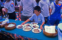 "Food, fun and entertainment at the """"taste of Honolulu festival"""". Young boy with pieces of cake"