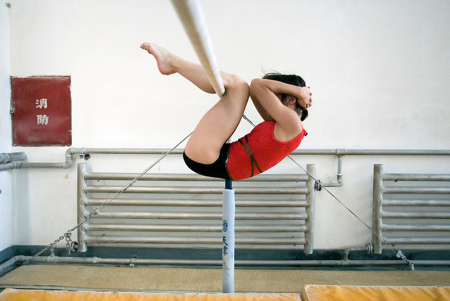 Jing Yang does sit-ups while hanging from a bar.