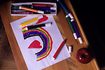Drawing colorful rainbow with multicolored markers at school