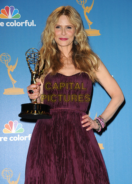 KYRA SEDGWICK.The 62nd Annual Primetime Emmy Awards held at Nokia Theatre L.A. Live in Los Angeles, California, USA. 29th August 2010.half length trophy winner purple strapless gown dress hand on hip beads bracelets .CAP/RKE/DVS.©DVS/RockinExposures/Capital Pictures.
