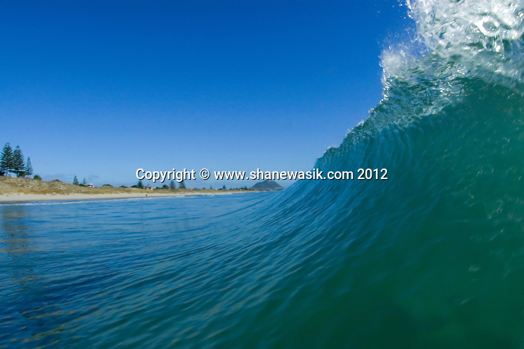 The summer swell is about to break upon reaching the Mount Maunganui shores. Spare a thought for the photographer a few moments after the shutter was released and washing machine started.