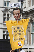 "London, UK. 26 July 2014. A T-shirt with a David Cameron mask and the slogan ""I love killing women & children. Protesters gather in Parliament Square and Whitehall after a march from the Israeli Embassy in Kensington to call for an end to the Israeli military action against the Palestinians in the Gaza Strip at a political rallye."
