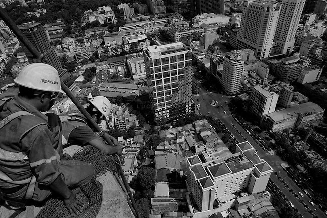 Construction workers build Vietnam's first skyscraper in downtown Saigon.  The completed financial tower will have 68 stories and a helicopter landing pad.