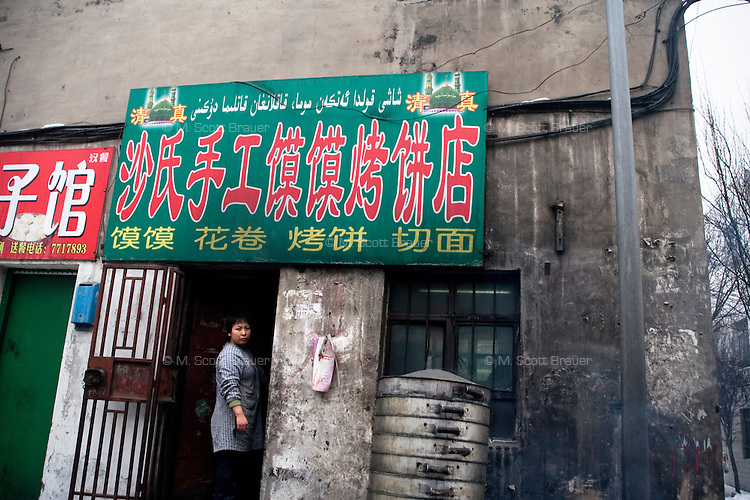 A bkaer stands in the doorway of a shop in a Han neighborhood in Urumqi, Xinjiang, China. The city is divided between Han and Uighur ethnicities, and violent clashes erupted between the groups in 2009.