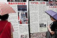 Two women are reading a billboard displayed in Hong kong on June 4 2010 for Tiananmen square massacre vigil.