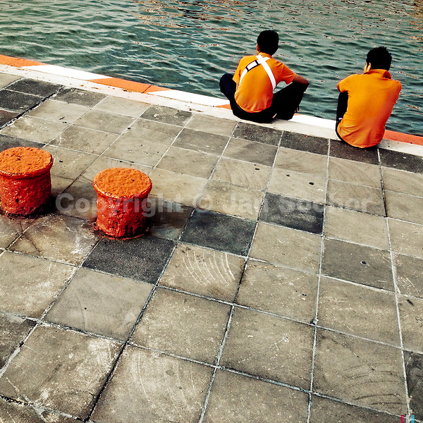 Mexican boys sit and relax on the wharf in the port of Veracruz, Mexico, 28 June 2015.