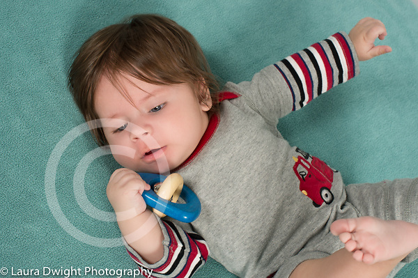 4 month old baby boy, lying on back, grasping toy with right hand and looking at it