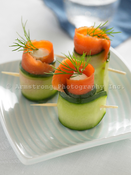 Toothpicks with lox wrapped in cucumber slices and cream cheese with fresh dill