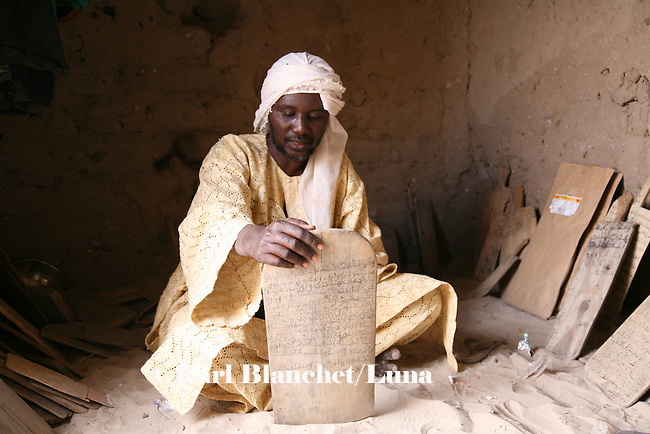 The marabout in his house in Timbuctu, Mali. The pupils are learning outside in the sahde of the wall. The marabout uses wooden boards to write versets. The coranic schools in Timbuctu are only open early in the morning and on Saturdays in order to allow pupils to attend the public school.