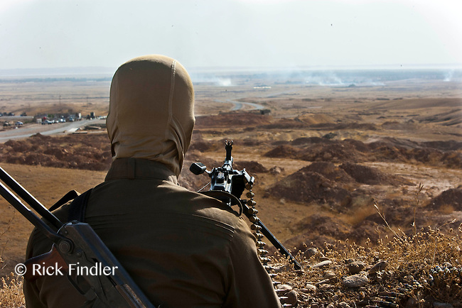"""DIYALA PROVINCE, KURDISTAN. 14.06.14 A member of the Kurdish armed fighters (also known as """"peshmerga"""") take aim over-looking the battle ground between other kurds and ISIS during clashes in Jalula, Diyala Province."""