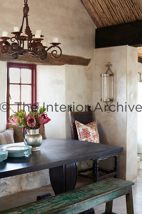 A wrought iron chandelier hanging above a wooden table and bench in a country stone dining room.