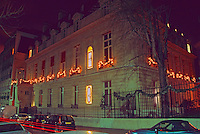 The exterior with neon signs of an eye and a mouth and Christmas decorations. At The Baccarat museum, shop, restaurant at the Hotel de Noailles in Paris. Designed by Philippe Starck.