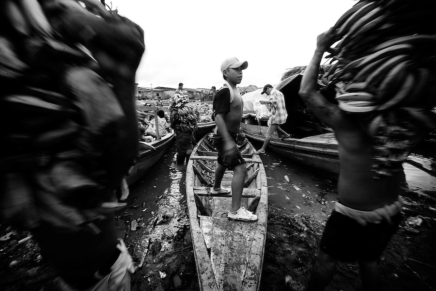 Iquitos, Peru, Jan. 13, 2007 - Young boys unload boats of bananas fresh from the jungle for the Belen Market. Made up of dozens of city blocks, the market is the primary market in Iquitos and it is the lifeblood of the city. Many of the residents of the floating city of Belen operate as both distibutors - by ferrying vegetables, produce, meat and medicines from the jungle to the market - and as merchants - where they sell these goods in outdoor stalls. The market provides the city with all of its needs, including clothing, tools, coal, wood, fruits, vegetables, fish and jungle meat, such as monkey, turtle, deer, and rodent. It is an informal market, meaning it operates outside of the law and it merchants do not pay any taxes. Though many of the goods are legal, many are not, such as monkey, turtle and during breeding season, Paische, a local prehistoric fish. Because it is such an integral part of the city, the police look the other way with regard to the illegal activity.