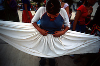 A girl praticing with a troupe for the local Guelaguetza dance festival looks over her skirt before taking to the floor of the town plaza to dance.