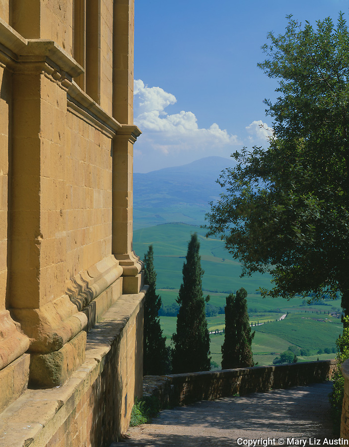 Tuscany, Italy:  Sun warms the cathedral wall in Pienza's Piazzo Pio II and a stone pathway leads to views of the rolling hills and farms of the Val d'Orcia