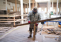 NWA Democrat-Gazette/CHARLIE KAIJO Hugo Rodriguez of Wilson Flooring Inc. measures wood panels for flooring, Thursday, February 8, 2018 at the old Dollar Saver building in Rogers.<br />