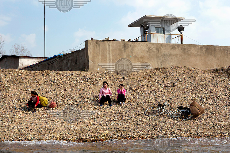 A group of women, seen from a Chinese tour boat travelling along the Yalu River (the border between China and North Korea), sit on the river bank on the North Korean side of the river. /Felix Features