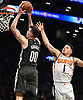 Rodions Kurucs #00 of the Brooklyn Nets, left, takes an alley oop pass from half court and dunks during the second quarter of an NBA game against the Phoenix Suns at the Barclays Center in Brooklyn, NY on Sunday, Dec. 23, 2018.
