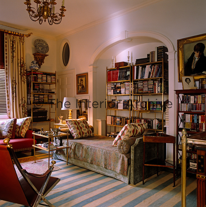 A series of open gilded bookshelves lines the walls of this living room
