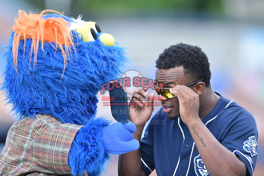 Asheville Tourists player Terry McClure (5) performs with a character from the SweetRight Brothers during a game against the Augusta GreenJackets at McCormick Field on August 6, 2016 in Asheville, North Carolina. The GreenJackets defeated the Tourists 11-4. (Tony Farlow/Four Seam Images)