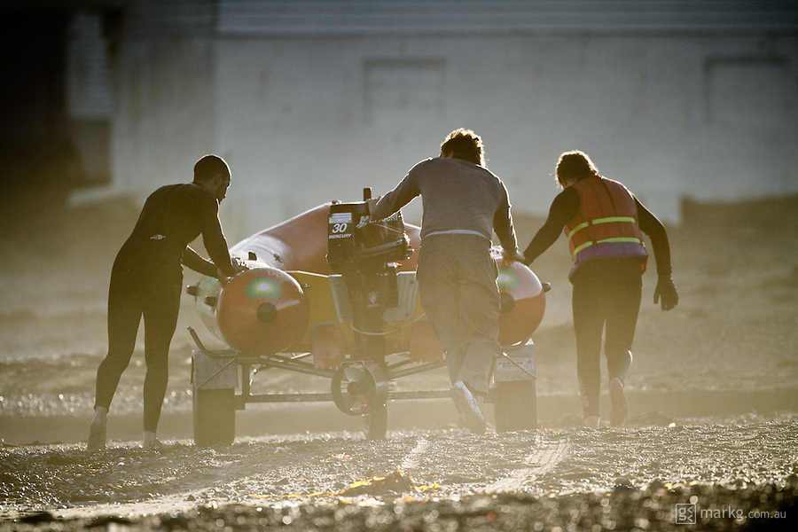Members of the Lyall Bay SLSC push a trailer loaded with an IRB (inflatable rescue boat) up the beach after a late afternoon training session at Lyall Bay