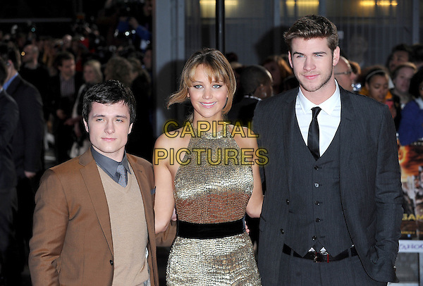 Josh Hutcherson, Jennifer Lawrence and Liam Hemsworth.European Premiere of 'The Hunger Games' at Cineworld at the O2 Arena, London, England..March 14th 2012.half length brown suit jumper sweater gold sleeveless dress black belt grey gray suit waistcoat .CAP/BEL.©Tom Belcher/Capital Pictures.