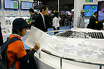 DECEMBER 10, 2009 - TOKYO - JAPAN: Kids are looking at a 3D concept city model on Sharp booth during the Eco-Product 2009 in Tokyo Big Sight. Some 700 exhibitors introduce their consumer goods, industrial materials, energies, finance and various services during three days. New environmental technologies and services that aim to change conventional wisdom, and new business models that aim to solve specific problems, including company coalitions and regional cooperation are displaying. In addition, 20,000 students in the Kanto Region as a school activity, and families can experience the low-carbon lifestyle of the near-future. 180,000 visitors are expected to attend (photo by Laurent Benchana/Nippon News).