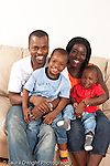 Portrait of family at home sitting on couch parents and sons ages 3 and 12 months old vertical
