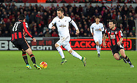 Gylfi Sigurdsson of Swansea (C) attempts to get past Charlie Daniels (L) and Harry Arter of Bournemouth (R) during the Barclays Premier League match between Swansea City and Bournemouth at the Liberty Stadium, Swansea on November 21 2015