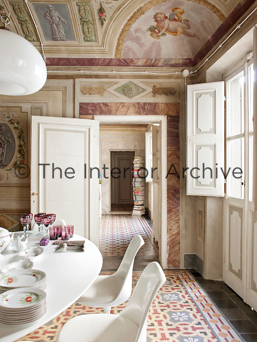 In a dining room in the Palazzo Orlandi,  a modern white Eero Saarinen Tulip table and chairs contrast with, yet compliment, the traditional richly decorated walls by Luigi Catani, a leading 18th century fresco painter.