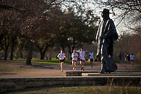 A group of runners and joggers pass by the Stevie Ray Vaughan Memorial Statue on beautiful sunny day on the Lady Bird Town Lake hike and bike trail
