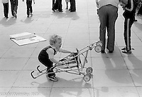 Toddler trying to pick up a buggy at the Education Centre, Festival & Gala Day, Wester Hailes, Scotland, 1979.  John Walmsley was Photographer in Residence at the Education Centre for three weeks in 1979.  The Education Centre was, at the time, Scotland's largest purpose built community High School open all day every day for all ages from primary to adults.  The town of Wester Hailes, a few miles to the south west of Edinburgh, was built in the early 1970s mostly of blocks of flats and high rises.