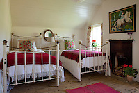 A pair of wrought iron beds in the guest room is dressed with blankets and cushions