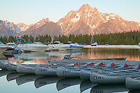 The first light of sunrise projects a warm glow on Mount Moran and the still surface of Jackson Lake and Colter Bay, full of sleeping boats and canoes.  Grand Teton National Park, Wyoming, USA
