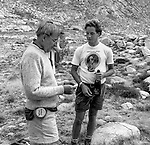 "Michael Adams Ansel's son reads a note while Matthew Weston Edward Weston's grandson holds bottle of Champaign from the Sierra Club.<br /> <br /> In August of 1987, the family and friends of Ansel Adams made a trip to Mount Ansel Adams to honor Ansel by putting his ashes on the mountain.  Leading the trip were Dr. Michael Adams and his wife, Jeanne, their son, Matthew, and daughter, Sarah.  Also in the group were Ansel's daughter, Anne Adams Helms, and her husband, Ken Helms, and Anne's daughters, Virginia (Ginny) Mayhew and Sylvia Mayhew Desin, and Sylvia's husband, Greg Desin.  Other members of the trip were Roger and Mitzi Hall, Matt Weston, Mrs. Desin (Greg's mother), and Billy Butler.  The Adams family invited me along with Leo Stutzin (Modesto Bee reporter) and my eldest son, Aaron Golub.  <br /> <br /> With some of us on horseback and others on foot, we began the hike at Tuolumne High Sierra Camp and headed to Vogelsang High Sierra Camp for the first night out.  The second day, we began by climbing through Vogelsang Pass, then descended by switchback down to Lewis Creek.  After climbing up from the creek we hiked by the Cony Crags before descending into the Lyell Fork of the Merced River ending up near Hutchings Creek at what is now referred to as the Ansel Adams Camp.  <br /> <br /> This camp was originally known generically as a Sierra Club Camp, but has more recently been referred to as Ansel Adams Camp because in 1934, Ansel led a Sierra Club outing to the Lyell Fork of the Merced River.  After the group climbed the then-unnamed peak that Adams called ""The Tower in Lyell Fork,"" they gathered around the campfire and agreed that the peak should bear Ansel's name.  The U.S. Geological Survey does not, however, permit naming features for living individuals, so the peak did not officially become Mt. Ansel Adams until 1985, one year and one day after his death.  Photo by Al Golub/Golub Photography"
