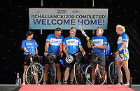 L-R The five cyclists Karen Munn, Mike Croft, Martin Snailham, local radio presenter, Chris Groves and Andy House pop a champagne on stage