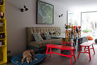 Brightly coloured furnishings, such as the neon-pink benches and canary-yellow shelving create enlivening accents in the pale grey of the kitchen and dining areas