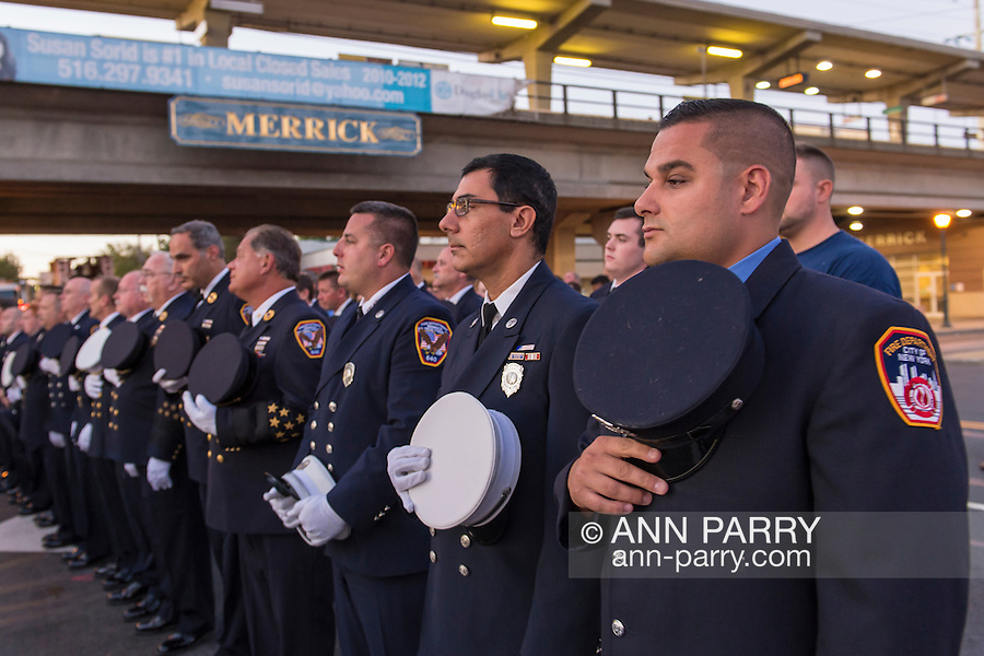 Merrick, New York, USA. 11th September 2015. Firefighters from Merrick and New York City stand in line and hold their caps over their hearts during Merrick Memorial Ceremony for Merrick volunteer firefighters and residents who died due to 9/11 terrorist attack at NYC Twin Towers. Ex-Chief Ronnie E. Gies, of Merrick F.D. and FDNY Squad 288, and Ex-Captain Brian E. Sweeney, of Merrick F.D. and FDNY Rescue 1, died responding to the attacks on September 11, 2001.