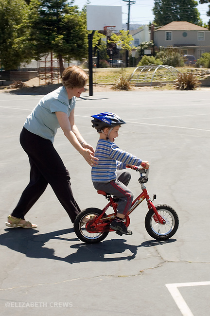 Berkeley CA  Mother helping determined four-year-old learn to ride two-wheeler  MR