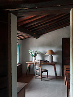 A corner of a bedroom has an intimate atmosphere. Traditional local materials were kept during the restoration of the house, such as the terracotta tiles on the floor and ceilings and the original massive wooden beams.